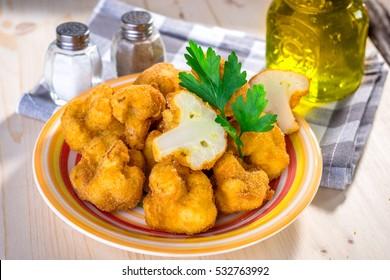 Breaded fried cauliflower on wooden background