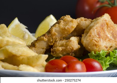 Breaded fried fish fillet and potatoes with lemon