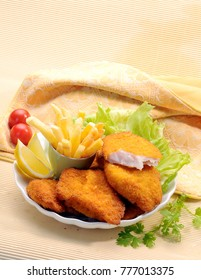 Breaded Fried fish with potato fries and tomato ketchup with lemon cherry tomato