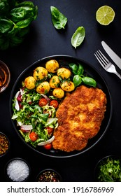 Breaded fried pork chop, fried potatoes and vegetable salad on black table