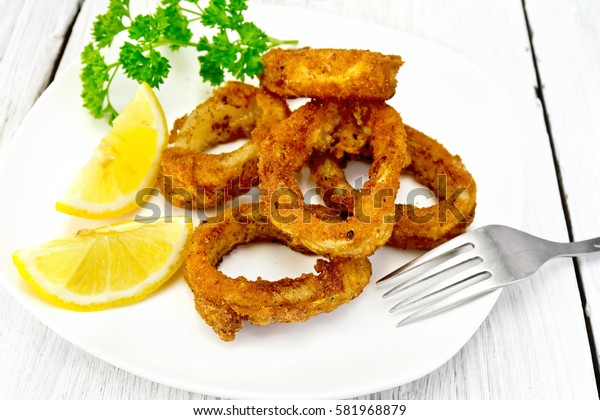 Breaded fried squid rings on a plate with slices of lemon and parsley on the background light wooden boards