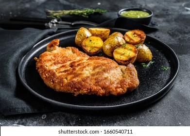 Breaded german weiner schnitzel with potatoes. Black background. Top view