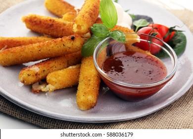Breaded mozzarella cheese sticks with tomato ketchup and mozza balls