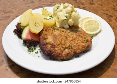 Breaded pork cutlet with boiled potatoes, cauliflower and hollandaise sauce