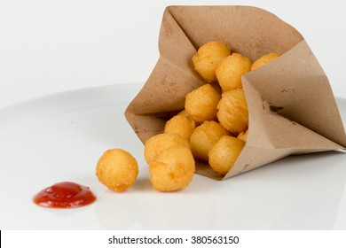 Breaded potato croquettes in a paper bag with ketchup isolated on white