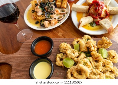 Breaded shrimp with ramekin sauce on a wooden table in a restaurant.