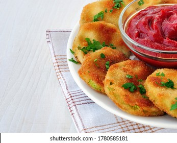 Breaded zucchini crisps with a bowl of ketchup on white wooden table