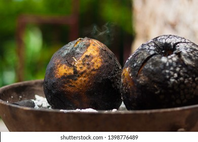 Breadfruit being roasted on a coal stove