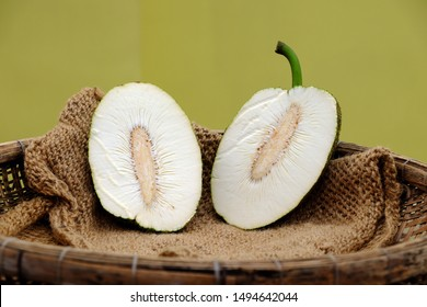 Breadfruit cut in half on burlap in bamboo basket on yellow background