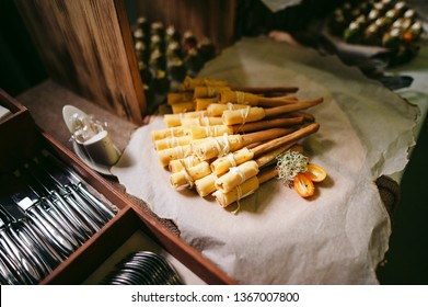 Breadsticks with cheese lie on a wooden stand on the buffet table. There is also cutlery