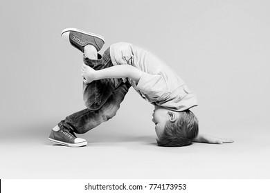 break dance kids. little break dancer showing his skills in dance studio. Hip hop dancer boy performing over studio background. Black and white photography