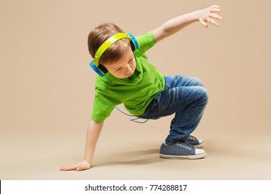 break dance kids. little break dancer showing his skills in dance studio. Hip hop dancer boy in headphones with smartphone against studio background