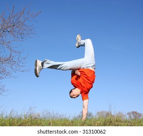 Break dance on the grass. Man in red t-shirt.  To see similar images, please VISIT MY GALLERY.