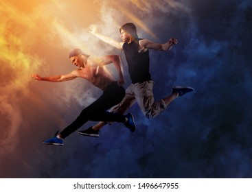 Break dance party. Two young man break dancing on smoke background