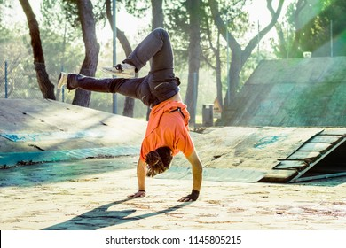 break dancer doing extreme sports trick in a urban park outdoors. parkour and break dance guy standing upside down while training on a sunny day.