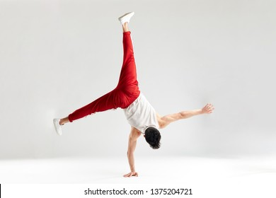Break dancer doing handstand stunt on one hand and splitted out legs over white studio background