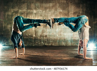 Break dancers team in old urban interior on wall background