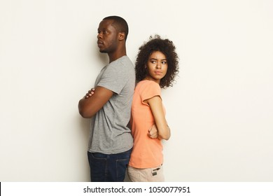 Break up or divorce. Upset young african-american couple standing back to back after quarrel, isolated white background, family misunderstanding concept, copy space
