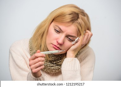 Break fever remedies. Take temperature and assess symptoms. High temperature concept. Woman feels badly ill sneezing. Girl in scarf hold thermometer and tissue close up. Measure temperature.