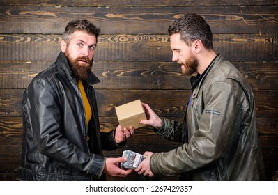 Break law. Dealer and buyer of illegal item. Buy illegal products. Cash money and box with forbidden goods exchange. Illegal deal concept. Money cash in hand of criminal man. Crime and illegal profit.