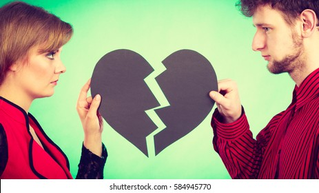 Break up and leave in relationship. Negative emotions between people in love. Young couple with two halves of broken heart. Lovers breaking up.