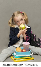 Break for lunch.Schoolgirl at lunch, eating an apple.Back to school.