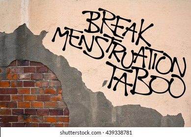 Break Menstruation Taboo - handwritten graffiti sprayed on the wall, anarchist aesthetics - Appeal to fight against false perception of natural cycle of bleeding as unclean, impure and dirty