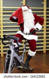 break - Santa Claus training on exercise bike at the gym