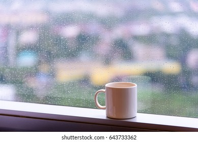 break time with a cup of coffee during raining at window with city view