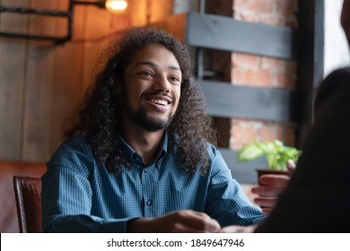Break time. Happy millennial mixed race male student employee with pleasant smile visiting cafe at lunchtime at workday, young biracial man resting relaxing at coffeehouse chatting talking with friend