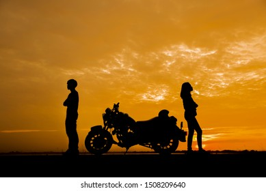 Break Up,Bad relationship,Anger,unhappy, concept.Silhouette of anger of couples love who are quarreling (argument) and standing back to back with Motorcycle against beautiful sunset in Thailand
