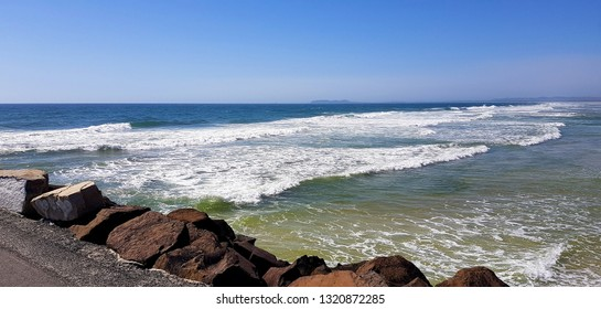 Break water rocks / boulders next to a beach with crashing waves under a blue sky.