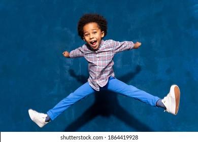 Frühstück fröhlich afrikanisch-süßer kleiner Junge, der im Sprung schwingt. Das lustige kleine, aufgeregte Tanzkind, das Spaß beim Hopfen hat. Positive Emotionen und Triumph-Konzept.