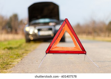 breakdown triangle stands near a broken car