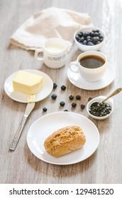 Breakfast with bagel, milk, butter, huckleberry jam and coffee