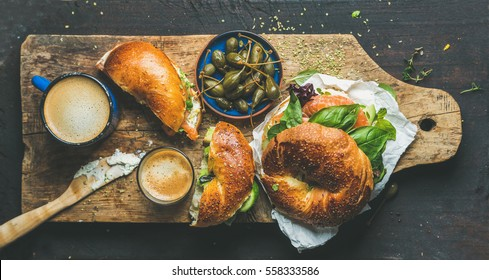 Breakfast with bagel with salmon, avocado, cream-cheese, basil, espresso coffee, capers in blue bowl, rustic wooden board over dark scorched background, top view. Healthy or diet food concept