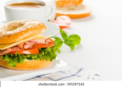 Breakfast of bagels with cheese and ham, salad and tomato close-up on white background