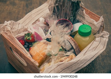 Breakfast basket with chocolate, foccacia, fruits, pastry products and juice on a wooden table. - Shutterstock ID 1949930248