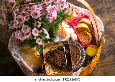 Breakfast basket with chocolate, quiches and flowers on a wooden table - Shutterstock ID 1921926878