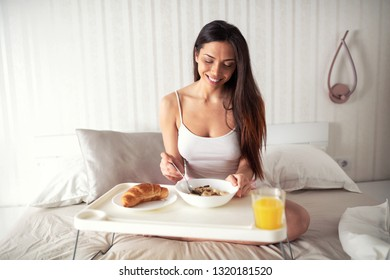 Breakfast in bed, cereals, baked goods and orange juice well served