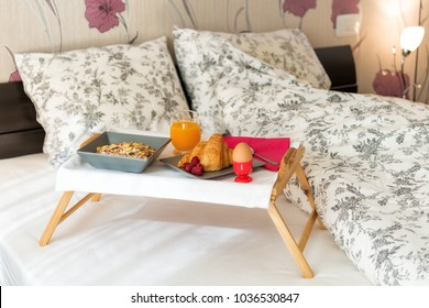 Breakfast in bed with cereals, fresh fruits, boiled egg, fresh orange juice and croissant on wooden tray