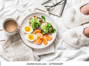 Breakfast in bed. Coffee, avocado sandwiches, boiled egg and tangerine on a light background, top view. Morning inspiration