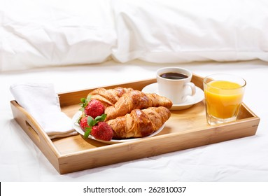 breakfast in bed with coffee, croissants, strawberries and juice