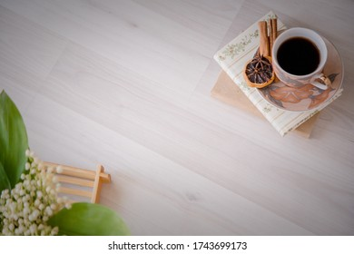 Breakfast in bed coffee a volume of books and Lily of the valley flowers on a bamboo tray. Cinnamon and orange slice romance love and care. Background for the title text.