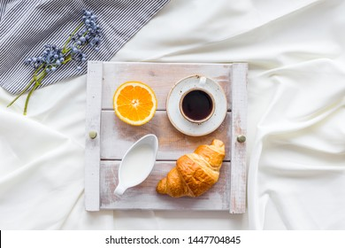 Breakfast in bed with croissant, coffee in cup with milk on tray on white bed background top view
