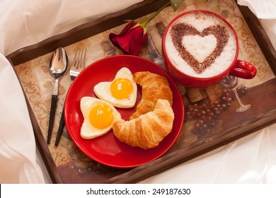 Breakfast in bed - eggs and croissants with a cup of coffee