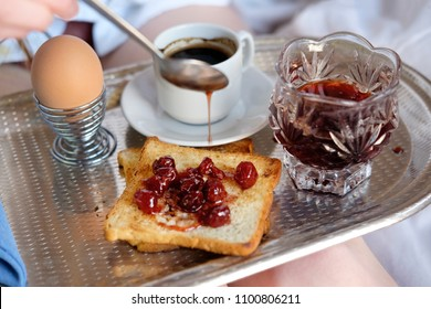 Breakfast in bed in hotel. Hand of woman spreading cherry jam on a toast.