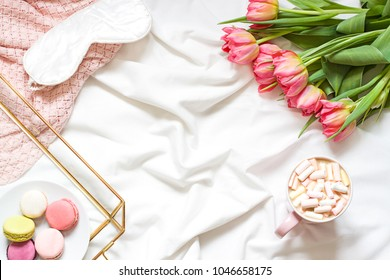 Breakfast in bed pastel flat lay frame composition with flowers, a cup o coffee and sweets. Concept  spring top view