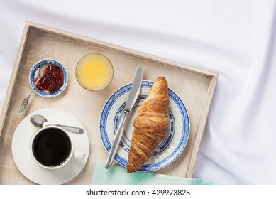 Breakfast in bed. Room service concept. Coffee, orange juice and a croissant on a tray.
