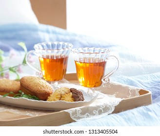 Breakfast in bed. Tea and bscuits on the blue bedding in the room full of sunlight.